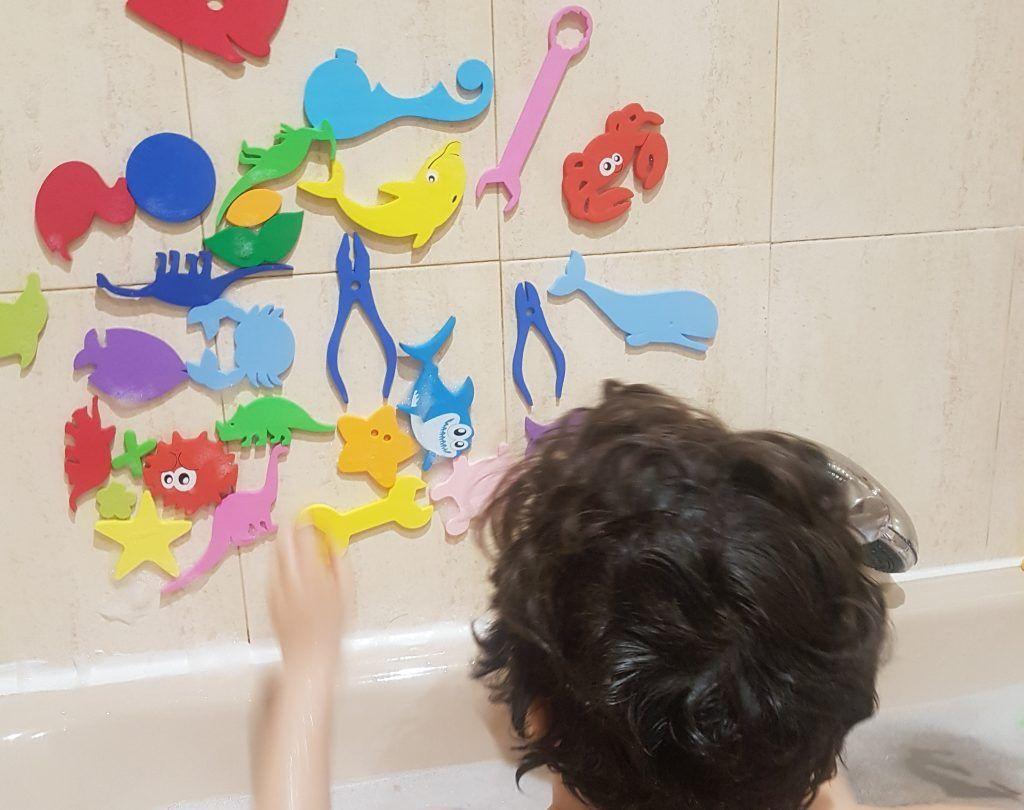 mi hijo de 6 años colocando figuras de goma eva en los azulejos de la pared sobre la bañera