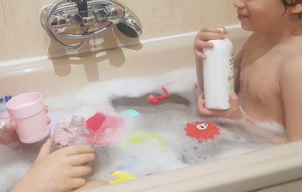 mis hijos de 6 y 8 años en la bañera, haciendo trasvases de agua con botes de champu, gel y vasos de plástico