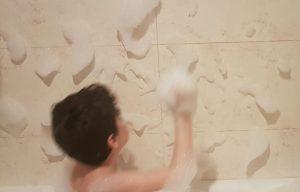 Mi hijo de 6 años formando nubes en la pared con la espuma de la bañera