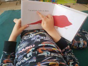 mi hijo de 6 años señalando con el dedo el texto de una pagina del cuento Me encanta bailar