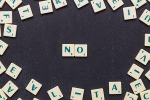 fichas de scrabble con la palabra NO en el centro