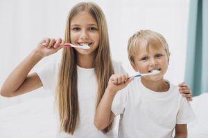 un niño y una niña cepillandose los dientes