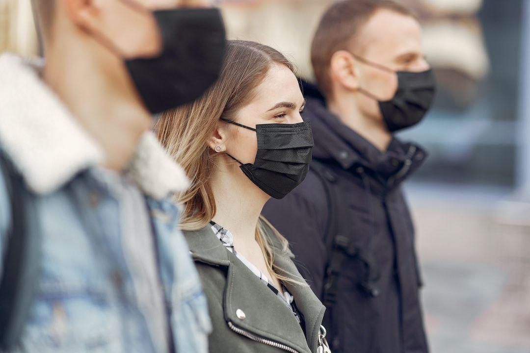 3 personas de perfil, en la calle, con mascarillas negras.