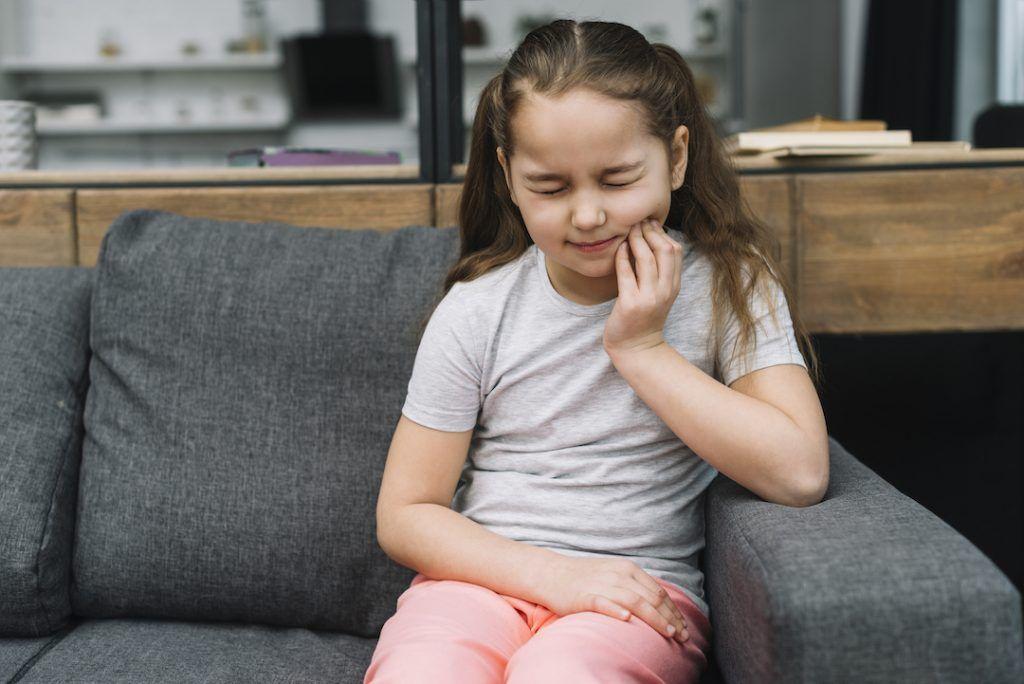 niña sentada en el sofa con la mano en su barbilla y cara de dolor de muelas