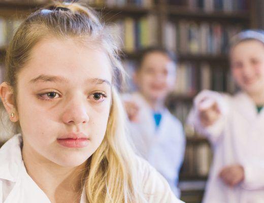 niña en el colegio llorando mientras otros niños la señalan riéndose
