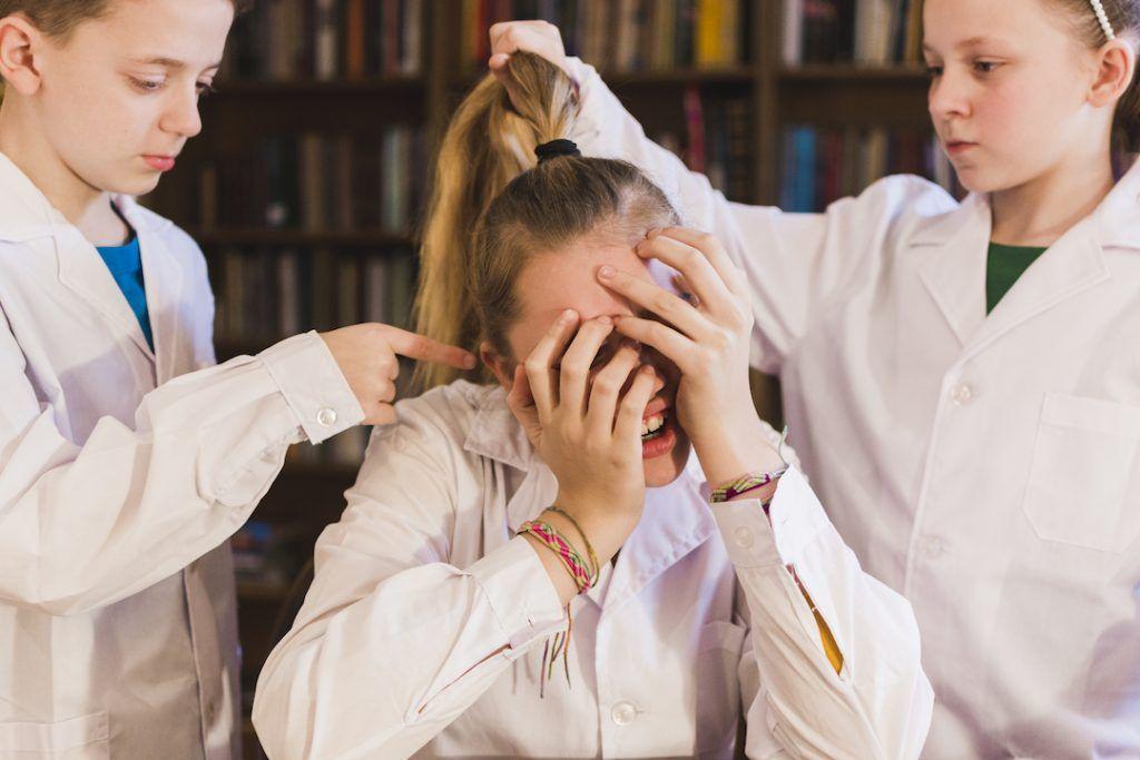 niña tapándose la cara mientras otros 2 niños la molestan y cogen del pelo