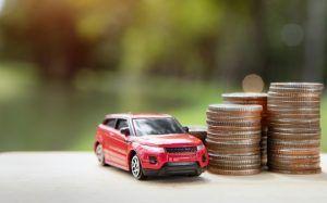 coche de juguete sobre una mesa, al lado de unas pilas de monedas