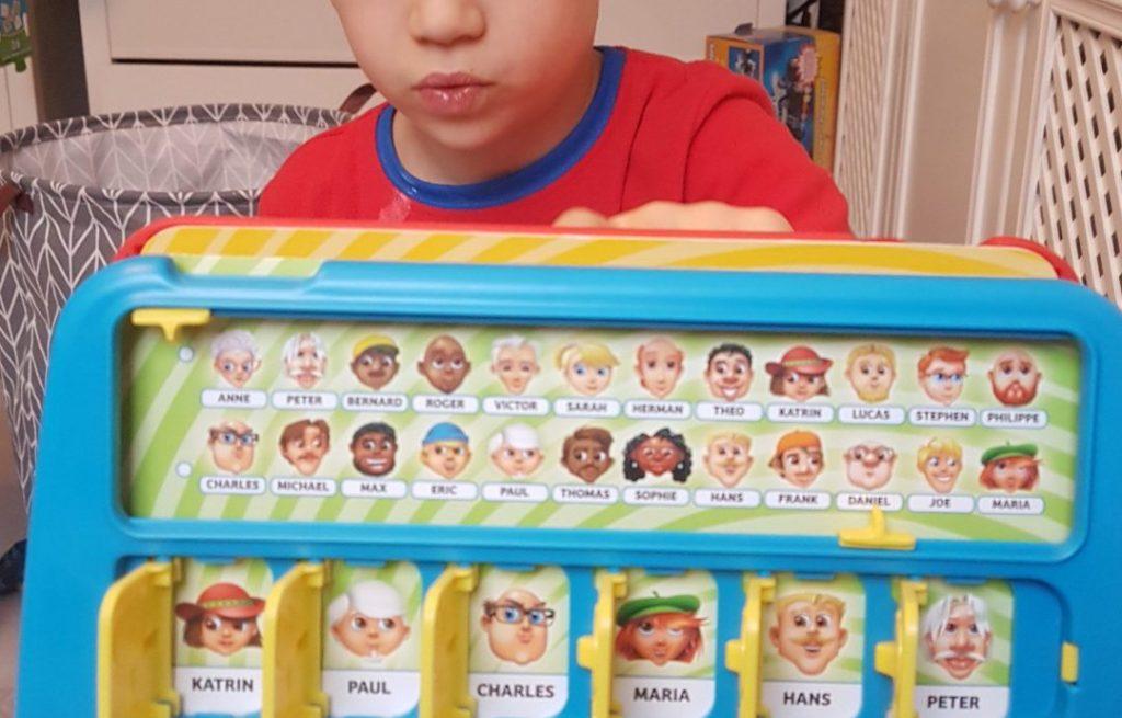 mi hijo de 6 años detrás del tablero del juego de mesa quién es quién