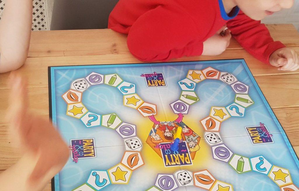 Mis hijos en la mesa de la cocina, en torno al tablero del juego Party Junior durante una partida familiar