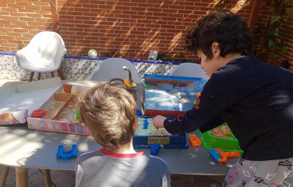 Mis hijos de 6 y 8 años sentados en la mesa de la terraza juigando con plastilina y arena mágica