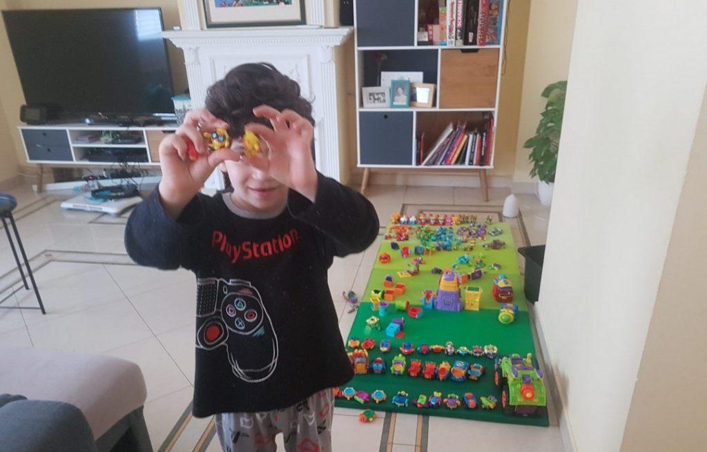 Mi hijo de 6 años de pie enseñando con ambas manos unos superzins. Detrás se ve el salón y una colchoneta en el suelo llena de superzings