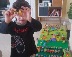 Mi hijo de 6 años de pie enseñando con ambas manos unos superzings. Detrás se ve el salón y una colchoneta en el suelo llena de superzings