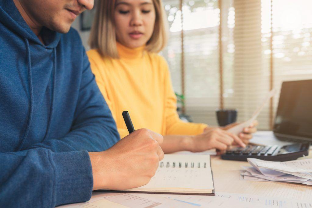 pareja de hombre y mujer sentados en un escritorio haciendo cuentas en un cuaderno