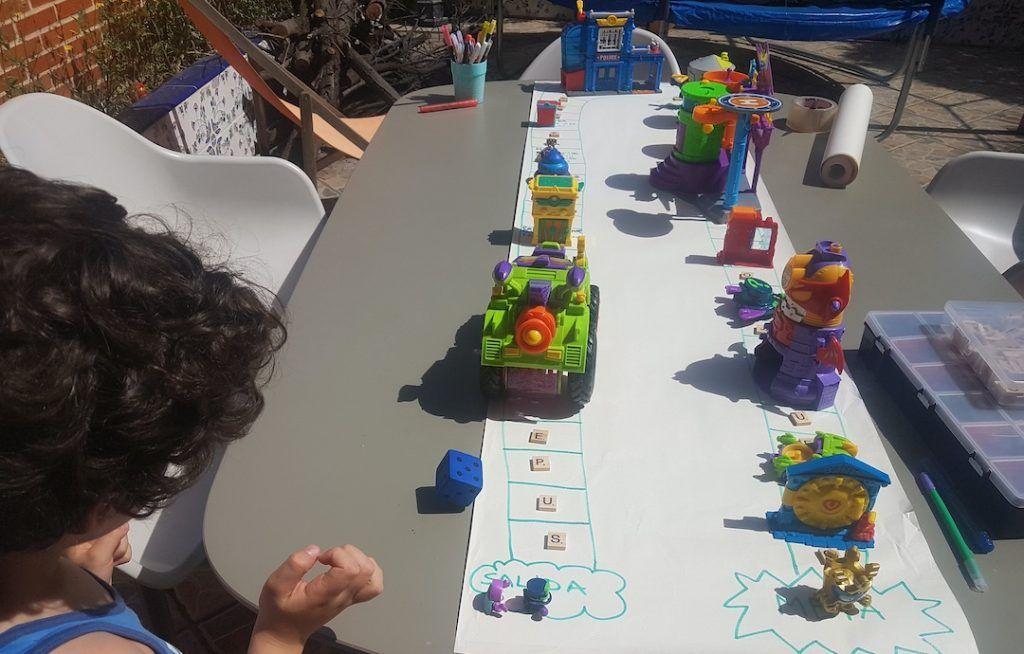 mi hijo de 6 años tirando el dado en la mesa donde está colocado el juego de superzings DIY que montamos