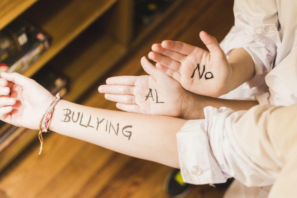 manos de 3 niños con la leyenda escrita No al bullying