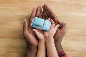 manos de un hombre palmas arriba, sosteniendo las de un niño que sujeta un coche de juguete