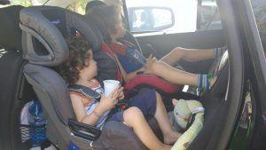 mis hijos con 3 y 5 años sentados en el coche en sus sillas a contramarcha