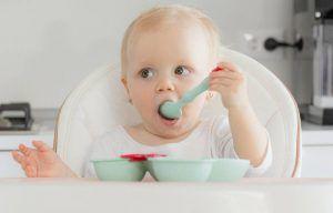 bebé rubio sentado en una trona comiendo con una cuchara