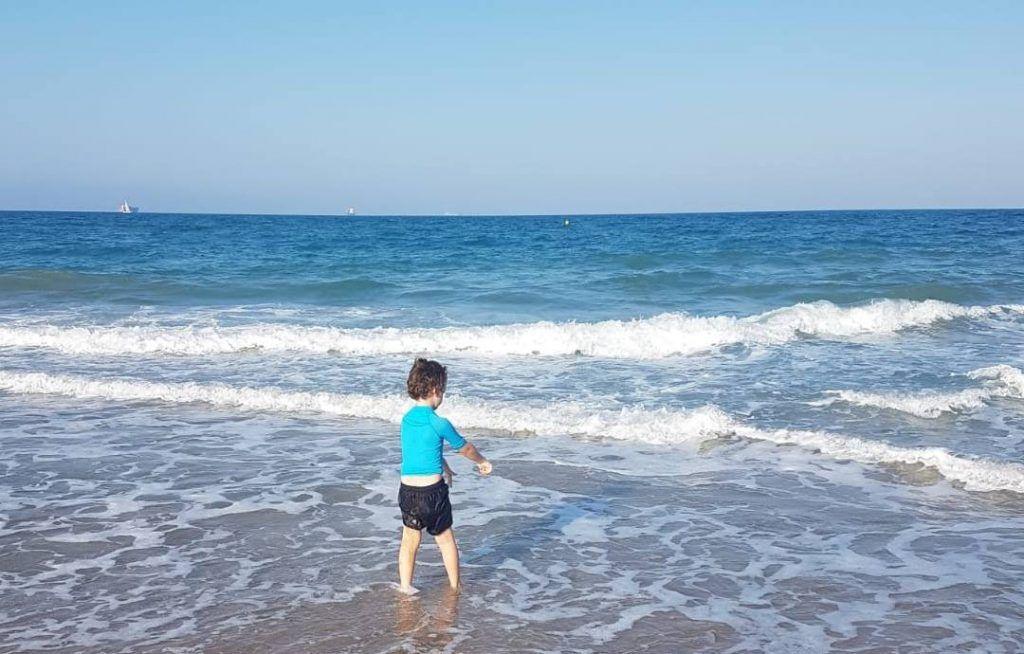 mi hijo mayor de espaldas, en la orilla del mar de Benidorm