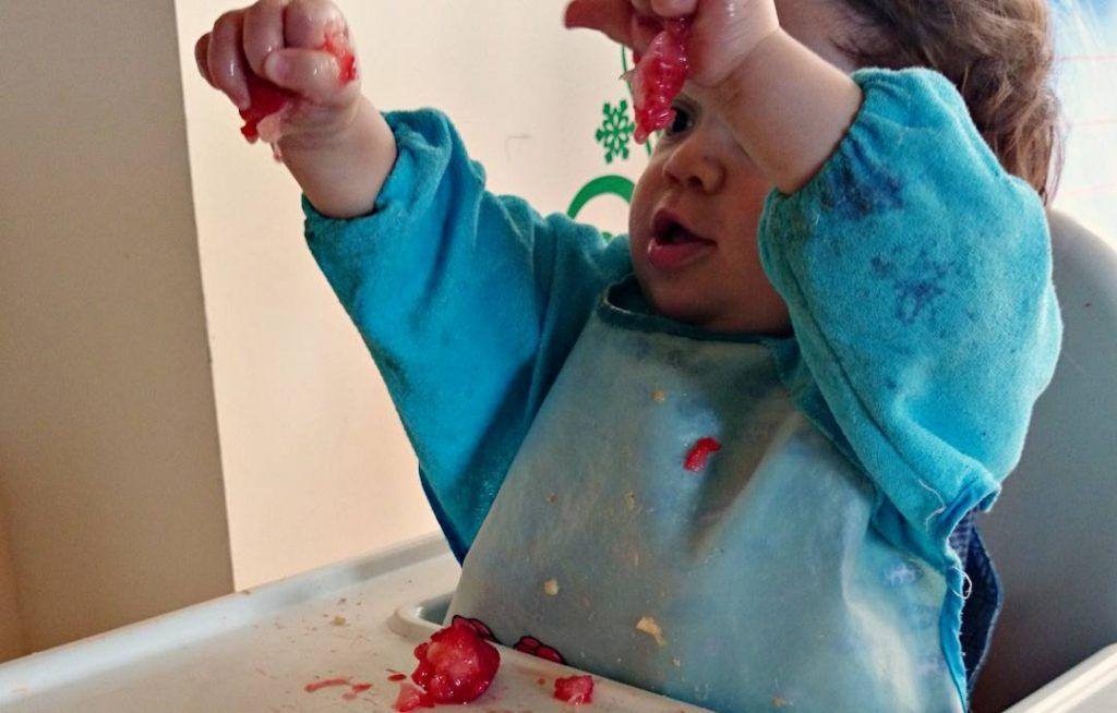 mi hijo sentado en la trona con los brazos extendidos hacia arriba aplastando en puño una fresa con cada mano.