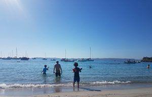 mis hijos de espaldas en la orilla del mar de Cerdeña con unos barcos de fondo