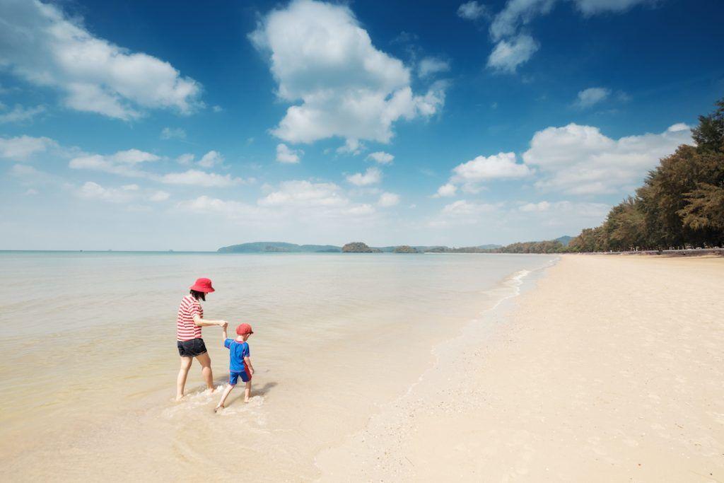 madre e hijo caminan por la orilla de la playa, con gorra y camiseta