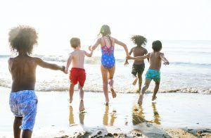 grupo de niños de espaldas corriendo hacia el mar