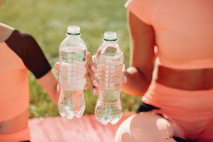 madre e hijo sentados en el parque con una botella de agua en la mano cada uno