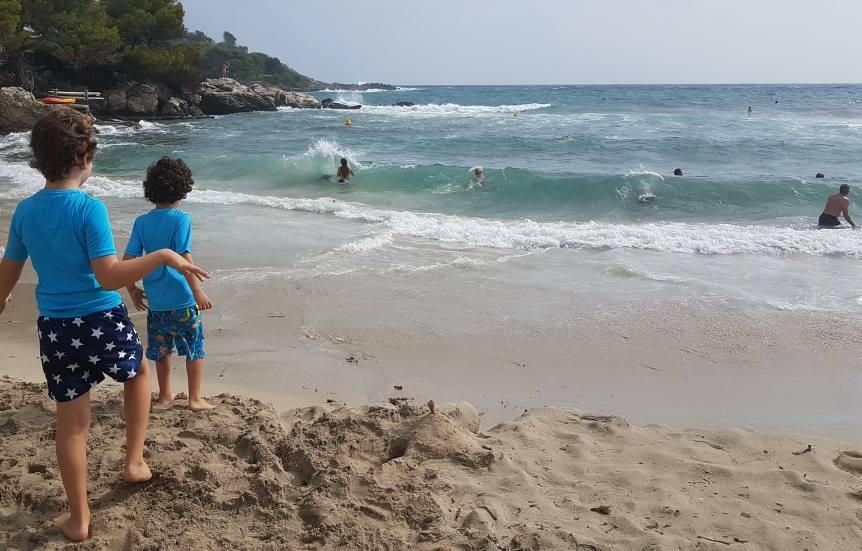 mis hijos corriendo hacia el mar en una cala de Mallorca