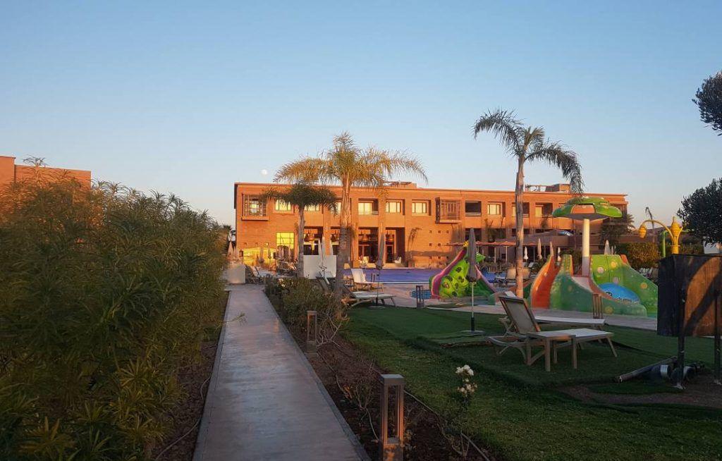 foto de un complejo hotelero con piscina, juegos infantiles y plameras en Marrakech