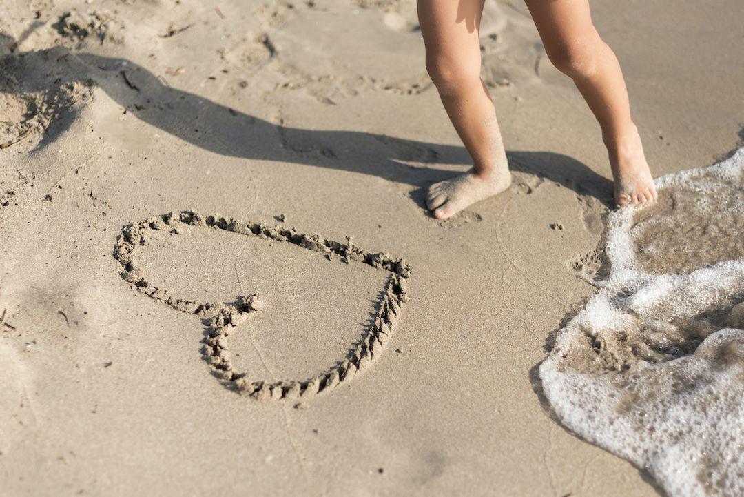 pies de un niño al lado de un corazón dibujado en la arena, en la orilla del mar