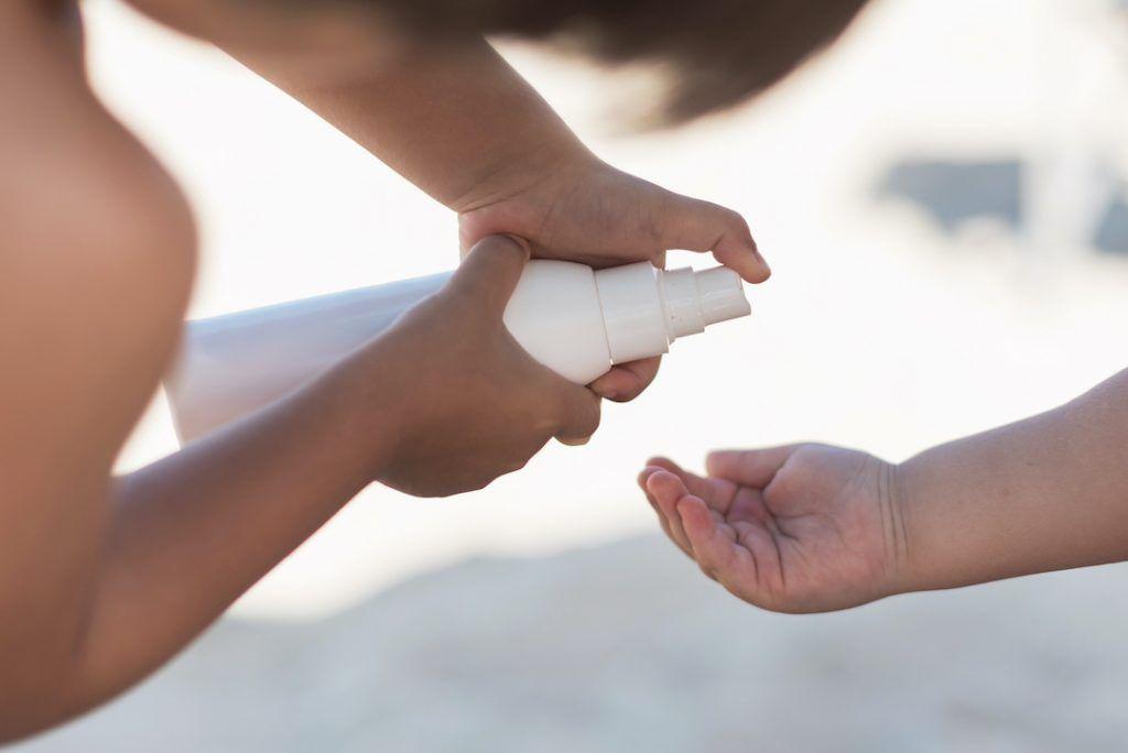 niño pone protector solar en la mano de un bebé