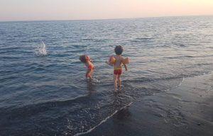 mi hijo pequeño y su primo en la orilla del mar de Torre del Mar, lanzando piedritas al agua