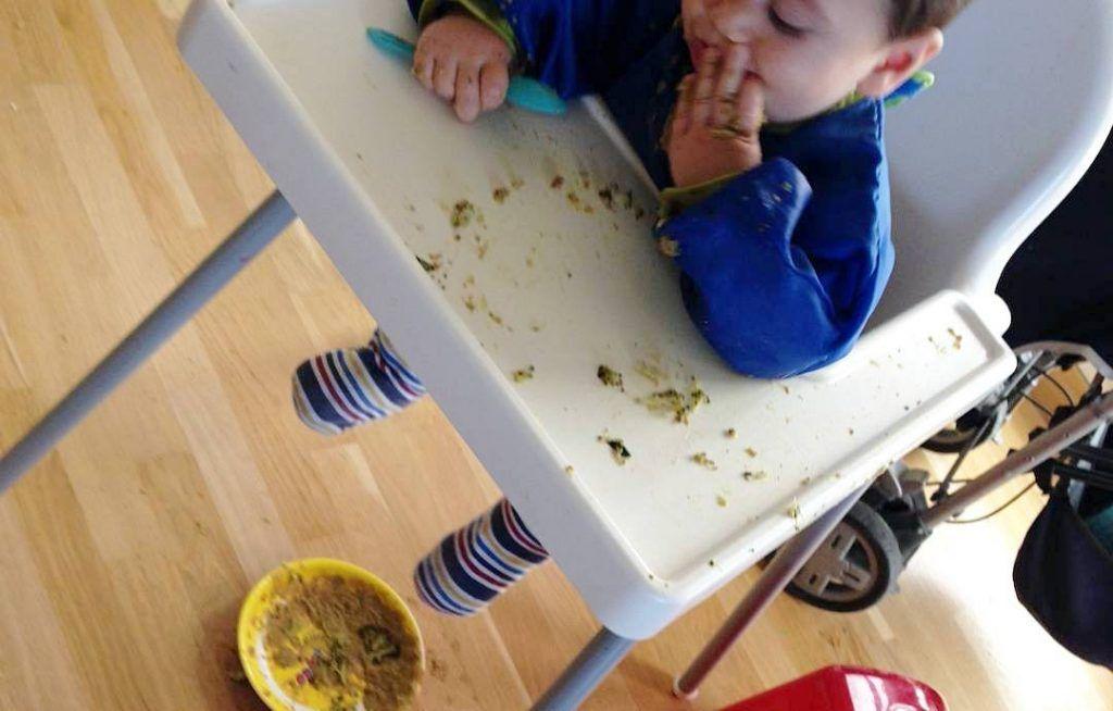 mi hijo pequeño comiendo con las manos sentado en la trona, en el suelo se ve el plato que ha lanzado