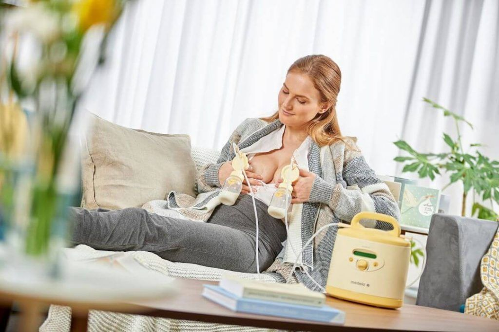 mujer sentada en sofá mientras se extrae leche con un sacaleches eléctrico doble que sujeta con las manos en cada pecho