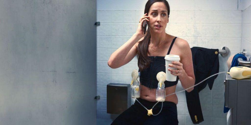 pantallazo de una escena de working moms con la protagonista sentada en un váter, hablando por el móvil, sosteniendo un vaso de café en la mano mientras tiene conectado un sacaleches eléctrico doble a su sujetador