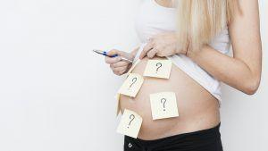 mujer embarazada con post its pegados en la tripa con signos de pregunta