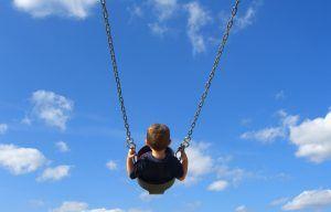 foto de un niño de espaldas columpiándose con el cielo azul con nubes blancas de fondo