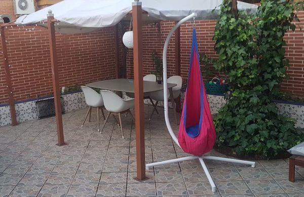 columpio de tela tipo huevo, color rosa, colgado de un soporte metálico de pie color blanco en una terraza