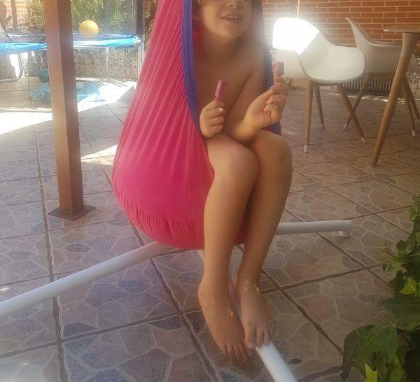 mi hijo con 8 años sentado en un columpio de tela tipo huevo, color rosa, colgado de un soporte metálico de pie color blanco en una terraza
