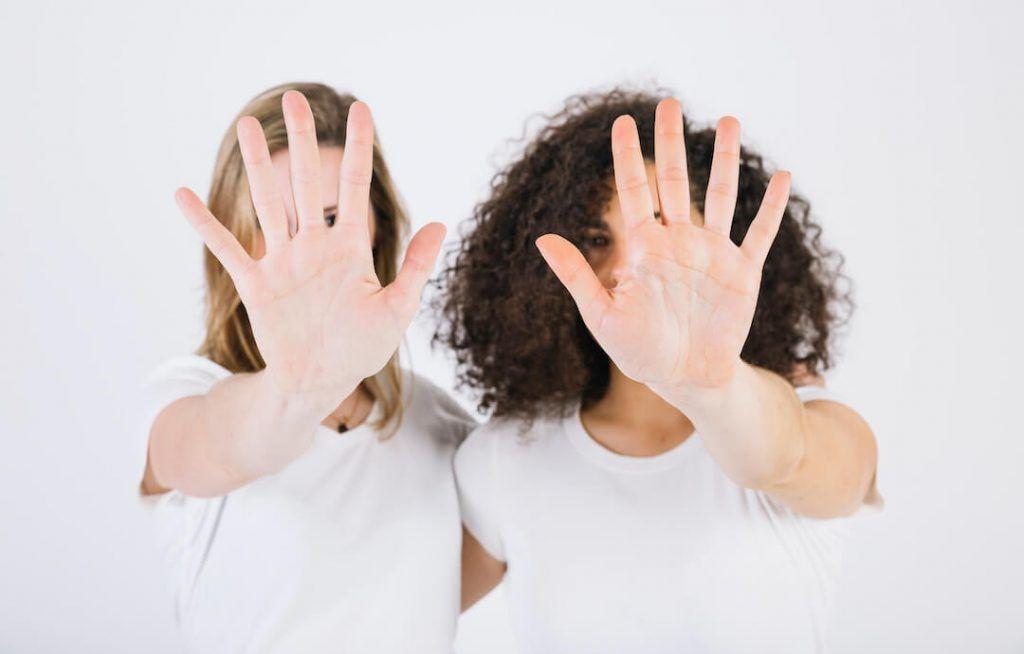 dos mujeres con la mano abierta en alto en signo de stop