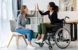 dos mujeres jóvenes chocando las manos. Una está sentada en una silla del salón y la otra en una silla de ruedas. Ambas sonríen