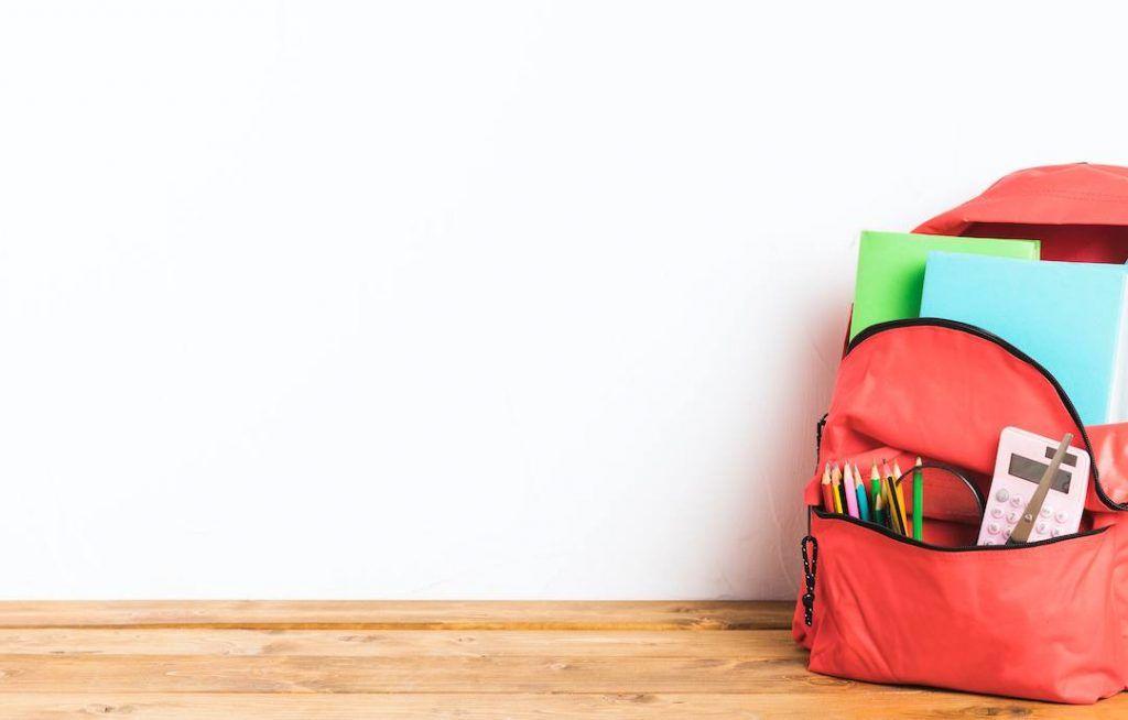 Mochila roja abierta con material escolar apoyada en un suelo de tarima.