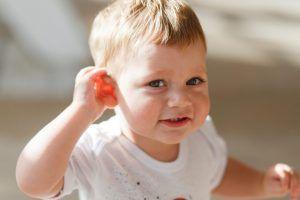 niño pequeño mira sonriendo poniendo una mano detrás de la oreja
