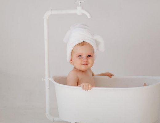 bebé sentada en una bañera blanca, con una toalla en la cabeza, sonriendo