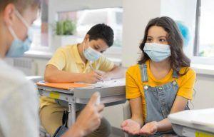 niños con mascarilla en el colegio poniendose gel de alcohol en las manos