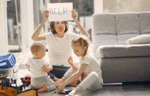 madre con 2 niños pequeños sentados en el suelo del salon. la madre tiene cara de agotada y sostiene en alto un cartel que dice HELP