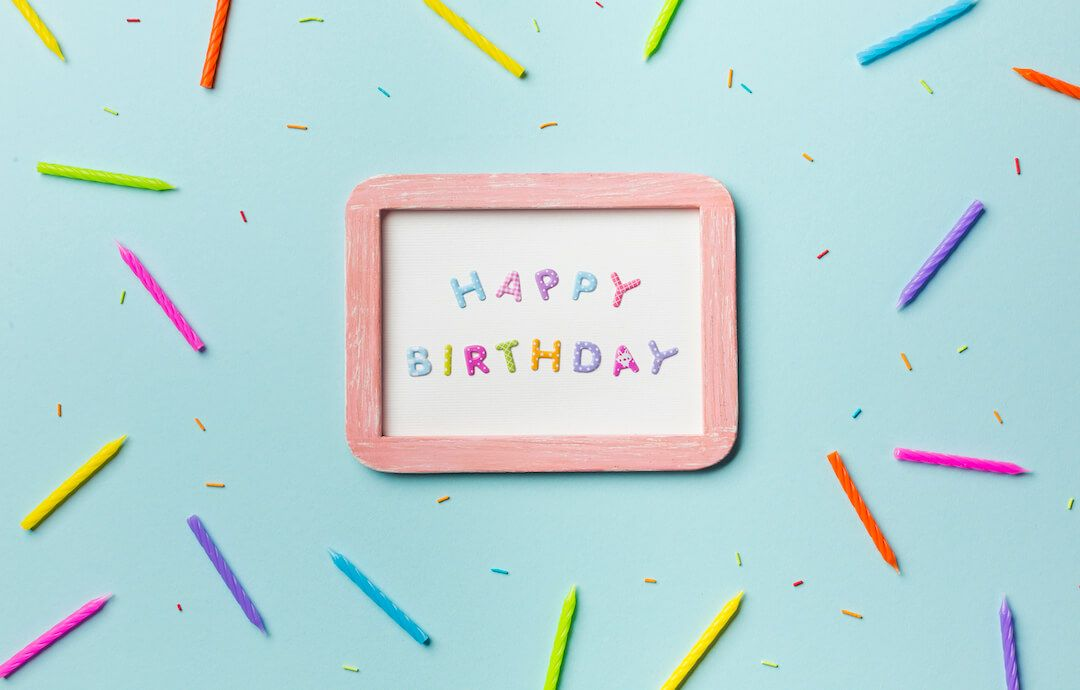 cartel de happy birthday sobre fondo azul rodeado de velas de colores