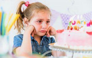 niña triste mirando a su tarta de cumpleaños