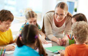maestra junto a niños y niñas, sentados en torno a una mesa redonda, sonriendo mientras se miran